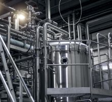 Modern beer factory, brewery concept. Steel tanks and pipes for beer production. Industrial background